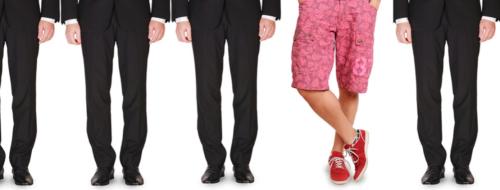 Odd Man Out. Menn i mørkdress med en mann i rosa shorts og røde sko.